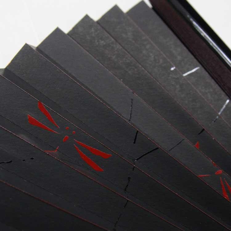 扇面には漆絵でとんぼと鮎をそれぞれ表現しました。脇に塗られた漆のツヤが扇子の折り山を彩ります。