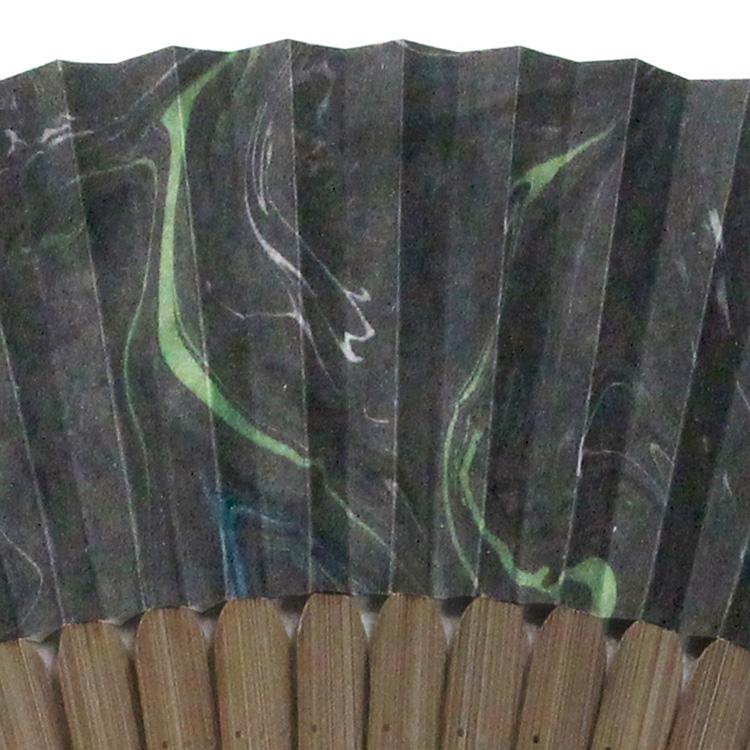 扇面には黒地に墨流しで模様が描かれています。