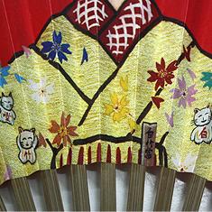 着物に描かれた招き猫と、舞妓が手に持った扇子には「白竹堂」の文字があしらわれています。