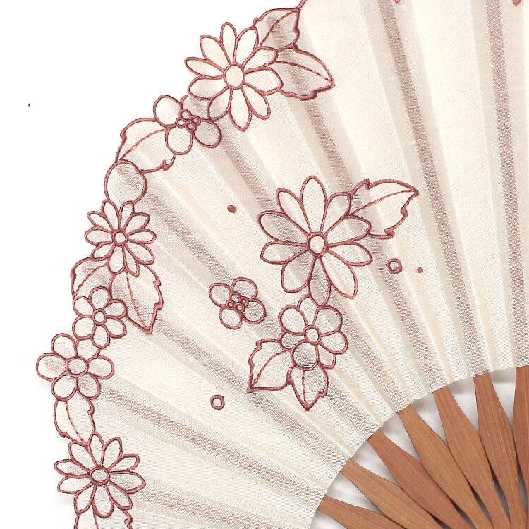 扇面の縁は波状にカットされ、縁取りにもマーガレットの刺繍が施された繊細な仕上がりです。